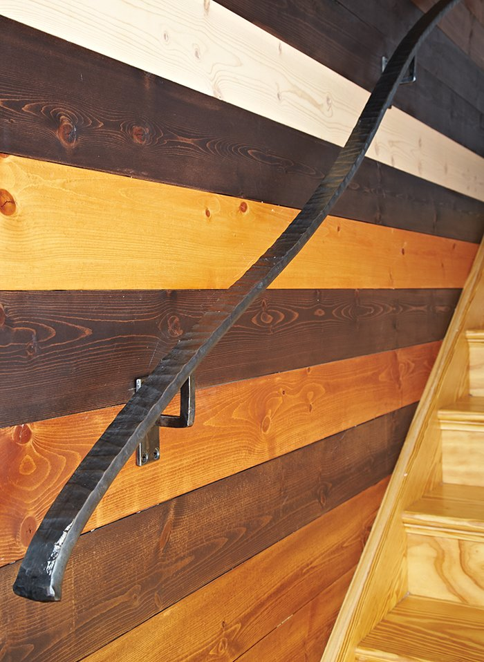 """One of the couple's favorite elements is the tongue-and-groove wall by the stairs. After staining and finishing the Douglas fir boards themselves, they gave their contractor a mathematical pattern developed by their teenage son, Griffin. """"It's like a puzzle for people to try and figure out,"""" Moss says. Carrier designed the curvilinear steel railing.  Photo 6 of 8 in Cost-Effective Family Home in Pittsburgh"""