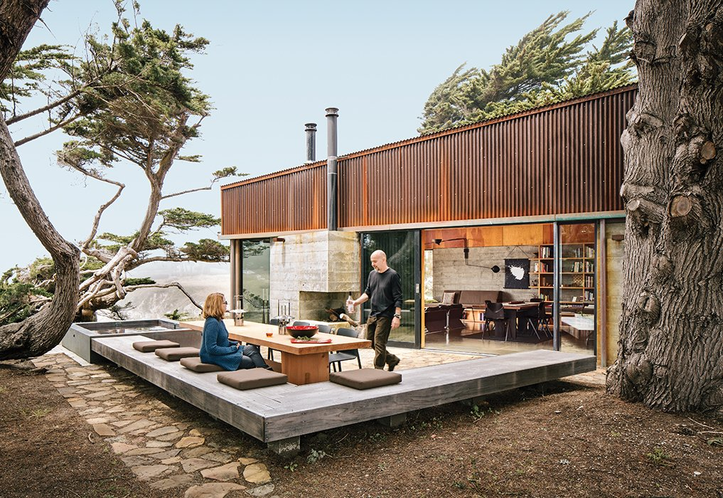 Exterior, House Building Type, Flat RoofLine, Metal Siding Material, and Concrete Siding Material Ramirez and his partner, Sarah Mason Williams, dine at a sequoia table by Redwood Burl next to a hulking juniper tree that they asked the architects to preserve as a centerpiece of the property.  Best Photos from Modern Home Joins a Storied Site on the Pacific Ocean