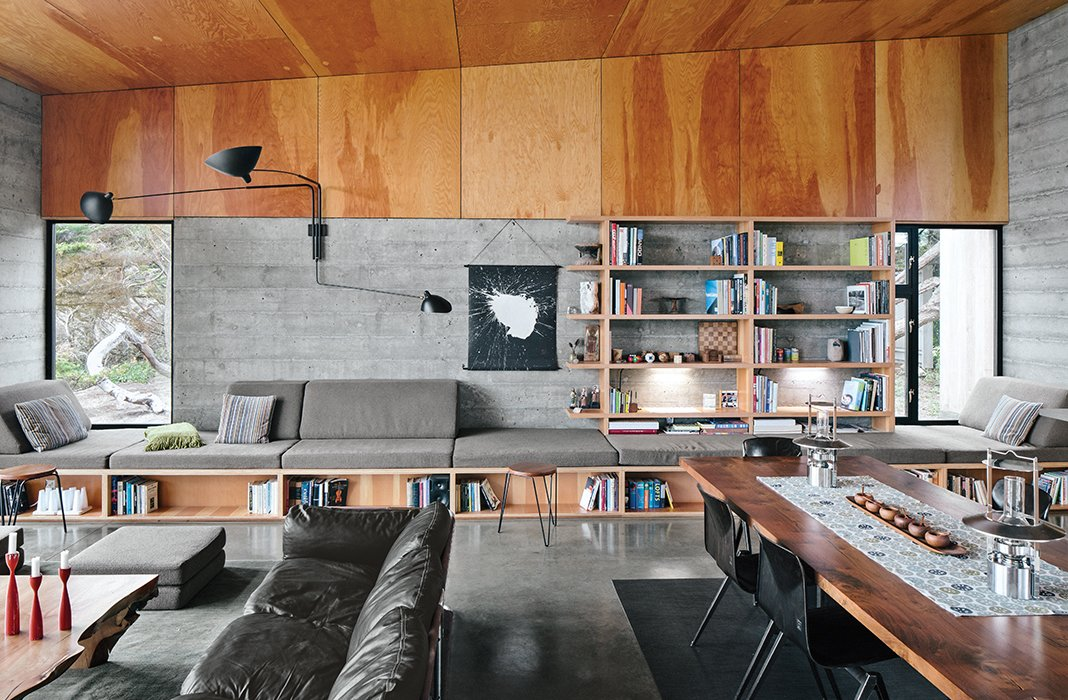 Norman Millar and Judith Sheine designed the built-ins in the living-dining area, which were made from vertical-grain Douglas fir. Vintage Dutch industrial chairs are arranged around a black walnut dining table that, like the madrone coffee table, is by Urban Hardwoods. Tagged: Living Room, Bookcase, Coffee Tables, and Bench.  Photo 9 of 9 in Modern Home Joins a Storied Site on the Pacific Ocean