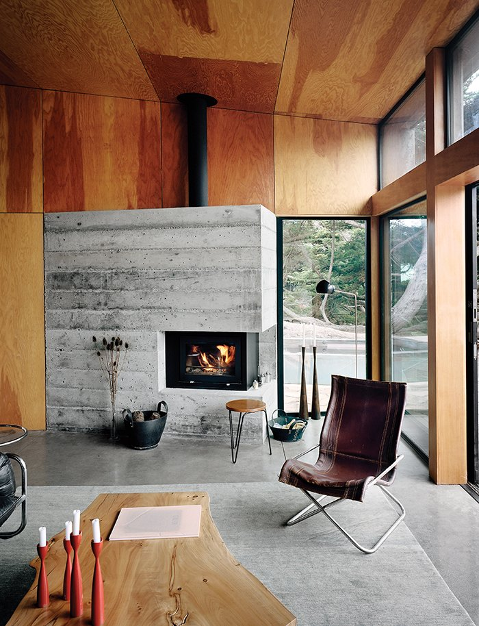 Living Room, Concrete Floor, Wood Burning Fireplace, and Chair The living room is furnished with vintage items, including a leather-and-chrome chair by Suekichi Uchida and a stacking stool by Florence Knoll.  Photo 3 of 9 in Modern Home Joins a Storied Site on the Pacific Ocean