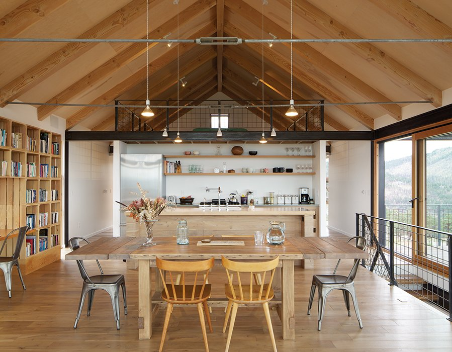 Del Gaudio made the pendants in the kitchen from rayon electrical cord, ceramic sockets, and Satco Par38 bulbs. She also designed the kitchen casing, which was fabricated locally in American black walnut left over from the floor. A mix of seating—vintage Paul McCobb Planner Group and newly purchased metal Tolix chairs—are arranged around a dining table from Restoration Hardware. Tagged: Dining Room, Storage, Chair, Light Hardwood Floor, Pendant Lighting, Table, and Shelves.  Photo 17 of 21 in 20 Dream Kitchens from Sustainable Retreat on a Fire-Devastated Site in Boulder