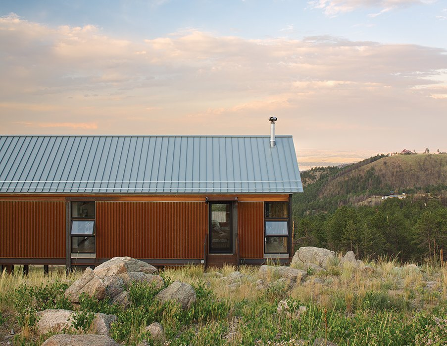 """Exterior, House Building Type, Wood Siding Material, and Gable RoofLine The fire-resistant structure is clad in corrugated Cor-Ten steel that has been left to rust for easy maintenance. Instead of fussy landscaping, the family spread seed for native grasses and wildflowers that they let fill in naturally.  Search """"cor ten steel"""" from Sustainable Retreat on a Fire-Devastated Site in Boulder"""