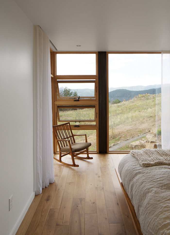 Bedroom, Chair, Light Hardwood Floor, Recessed Lighting, and Bed The house has no mechanical ventilation, only Hunter ceiling fans and opposing awning windows.  Bedrooms by Dwell from Sustainable Retreat on a Fire-Devastated Site in Boulder
