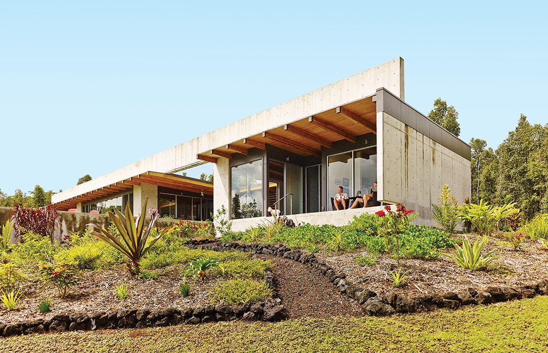 Back Yard, Exterior, Concrete Siding Material, House Building Type, and Flat RoofLine The defining gesture of a house on the Big Island of Hawaii by architect Craig Steely is a 139-foot-long, four-foot-tall concrete beam spanning the roof. Owners Craig Mayer and Rick Penland relax on the lanai, or porch.  Photo 2 of 25 in 25 Modern Homes That Kill it With Concrete from This House Conquers the Big Island in Hawaii