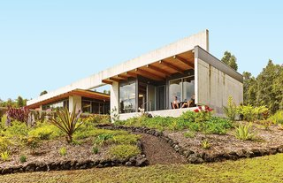 The defining gesture of a house on the Big Island of Hawaii by architect Craig Steely is a 139-foot-long, four-foot-tall concrete beam spanning the roof. Owners Craig Mayer and Rick Penland relax on the lanai, or porch.