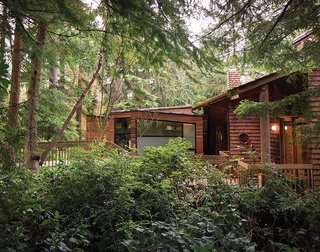 """The addition's beveled cedar siding will eventually weather to match the existing shakes, """"but it's different enough to distinguish the two,"""" says Wibowo. """"The window frames and metal roof color also match the dark bronze aluminum of the existing house, so it all blends."""""""
