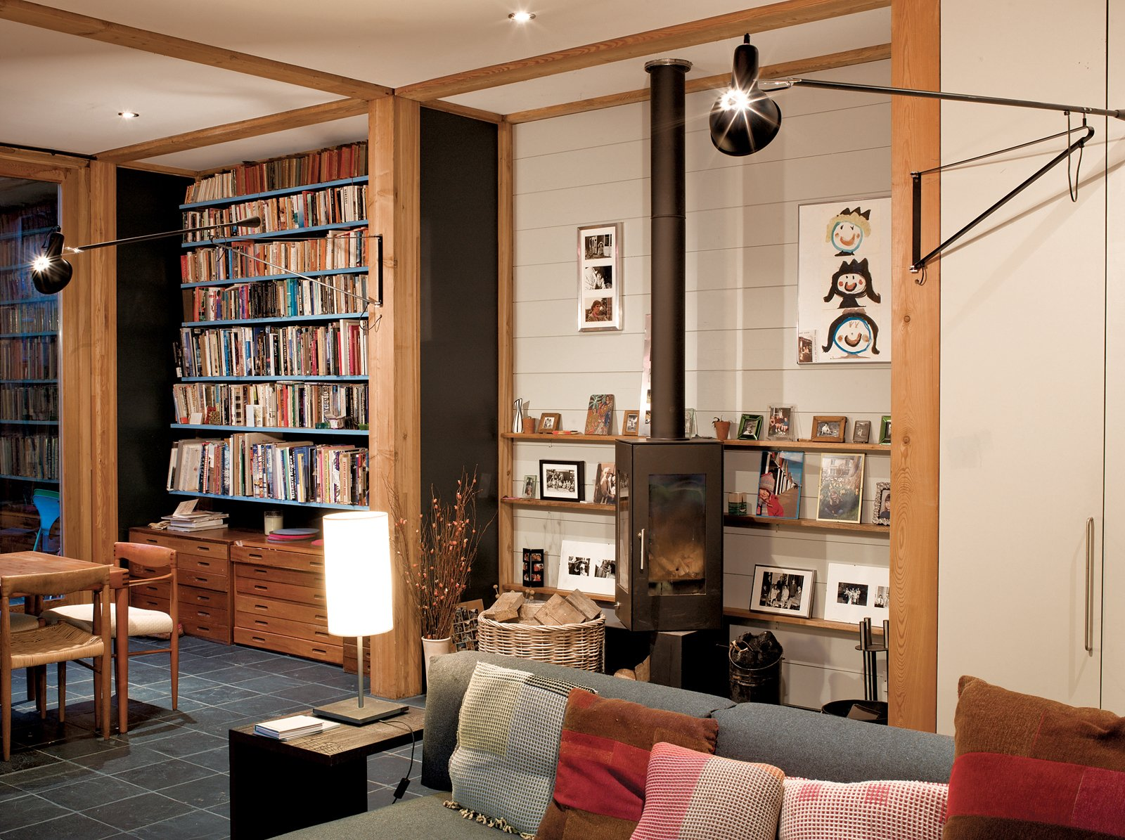 The main living area on the ground floor has plenty of storage, bookcases, and a Danish wood-burning stove, which pivots to throw heat and light in different directions.  Modern Wood-Burning Stoves by Megan Hamaker