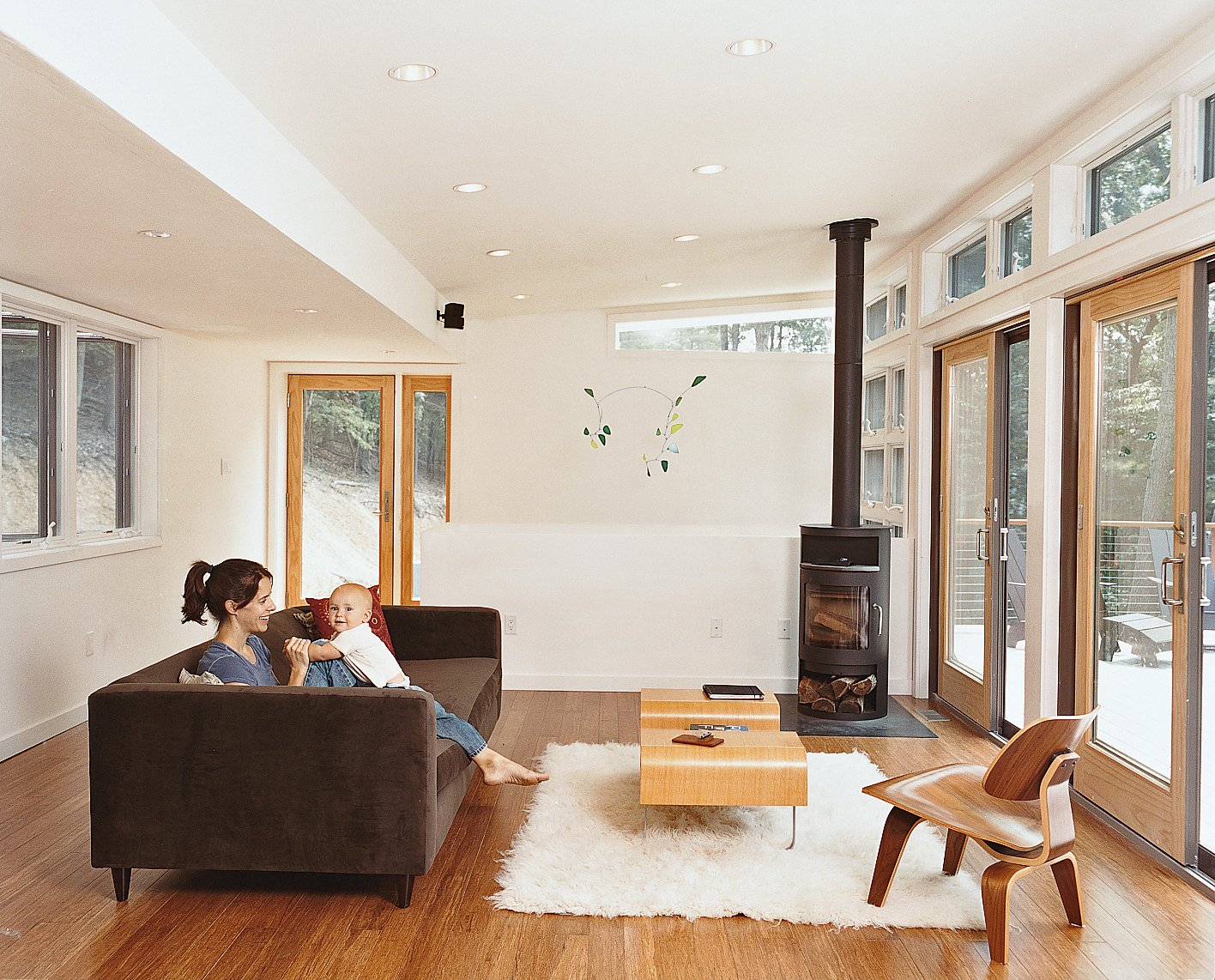A Movie sofa, by CB2, and a Rais wood-burning stove are in the living room. Tagged: Living Room, Sofa, Chair, Medium Hardwood Floor, Wood Burning Fireplace, and Ceiling Lighting.  Modern Wood-Burning Stoves by Megan Hamaker from Take Me Home