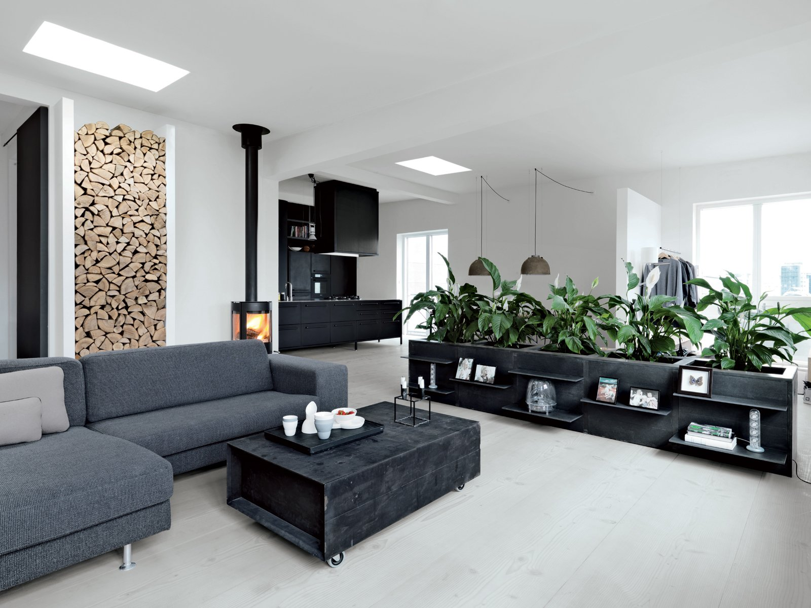 """The living room features a sofa from Engell; a suspended Parentesi lamp by Achille Castiglioni and Pio Manzù for Flos (Olsen's """"all-time favorite""""); and a wood-burning stove made by Aduro. The firewood nook set in the left wall is Jensen's own design. Olsen is responsible for the low planters around the perimeter, which she had fabricated from poured concrete framed in welded iron, with lacquered MDF panels for doors. """"Some people laughed because we'd never had plants in our apartment,"""" she says. """"So when we wanted a hedge, our friends were, like, Ok. Really? Good luck with that.""""  Modern Wood-Burning Stoves by Megan Hamaker from Converted Loft Fit for a Modern Family in Copenhagen"""