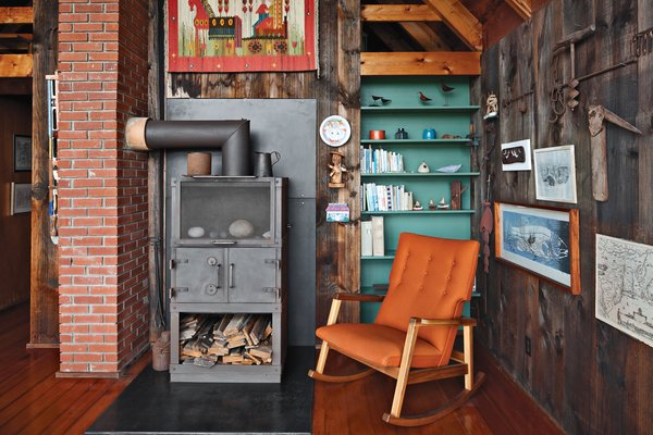 Inside the house, a relatively new Rais wood-burning stove is next to a Risom Rocker from Design Within Reach, a 2009 piece from the designer.