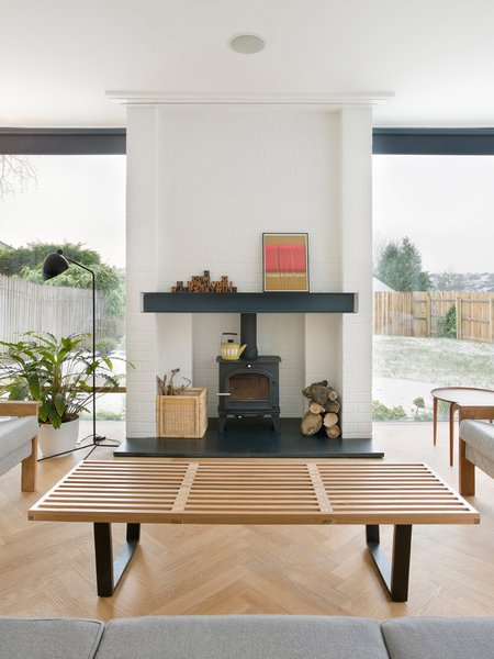 In the living room, a Nelson bench doubles as a coffee table, and a wood-burning stove from Cleanburn Stoves keeps the space warm.