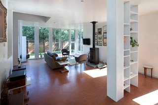 The living room at the front of the house benefits from the privacy afforded from the cedar screen and the light let in by a wall of windows. The wood-burning stove and collection of paintings give the modern home a bit of New England charm.