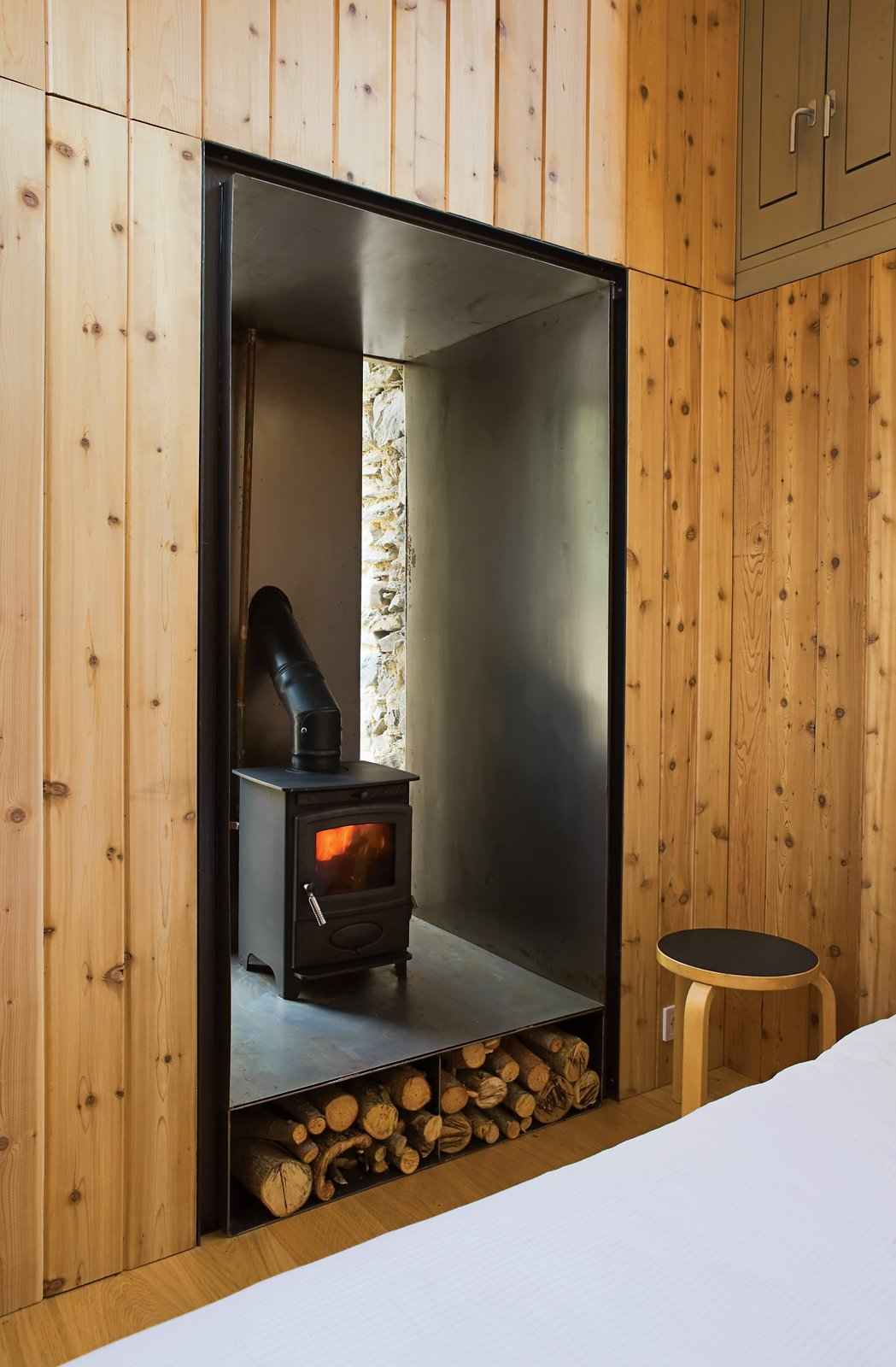 """To heat the small structure, Blee and Halligan installed a 17.75-inch-tall, 15.75-inch-wide, and 15.75-inch-deep wood-burning stove equipped with a built-in water boiler. The stove was built into an old doorway that was no longer needed. By wrapping the walls in sheet steel, Blee and Halligan made the area fire-resistant, and the warmth from the stove is amplified as it reflects into the room. Though it's handy in the winter, the stove-boiler combination is merely decoration in the summer: """"It's so hot that we just bathe in the river nearby,"""" Blee says.  Modern Wood-Burning Stoves by Megan Hamaker from A Couple Restores a Seemingly Hopeless Mill in France"""