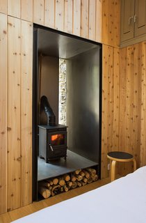 """To heat the small structure, Blee and Halligan installed a 17.75-inch-tall, 15.75-inch-wide, and 15.75-inch-deep wood-burning stove equipped with a built-in water boiler. The stove was built into an old doorway that was no longer needed. By wrapping the walls in sheet steel, Blee and Halligan made the area fire-resistant, and the warmth from the stove is amplified as it reflects into the room. Though it's handy in the winter, the stove-boiler combination is merely decoration in the summer: """"It's so hot that we just bathe in the river nearby,"""" Blee says."""