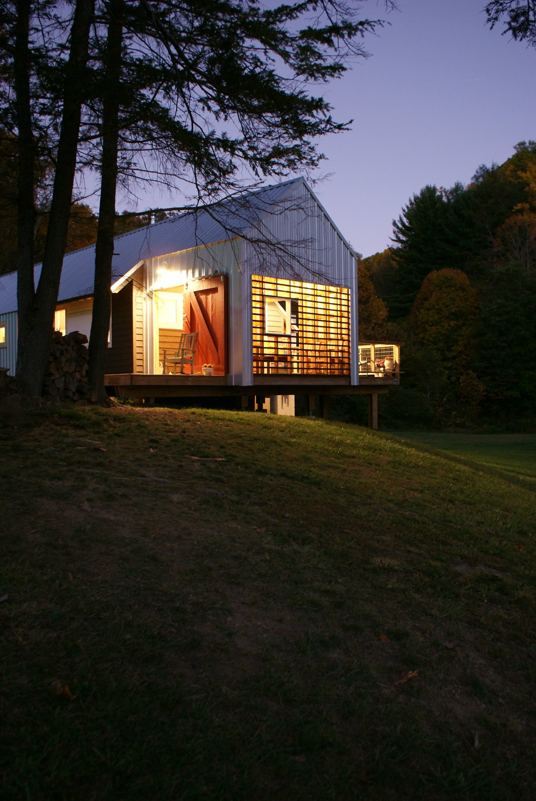 The new home's porches glow like lanterns at night.  Cabins & Hideouts