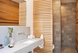 The master bathroom features a cedar screen and quartzite tiles by Walker Zanger.