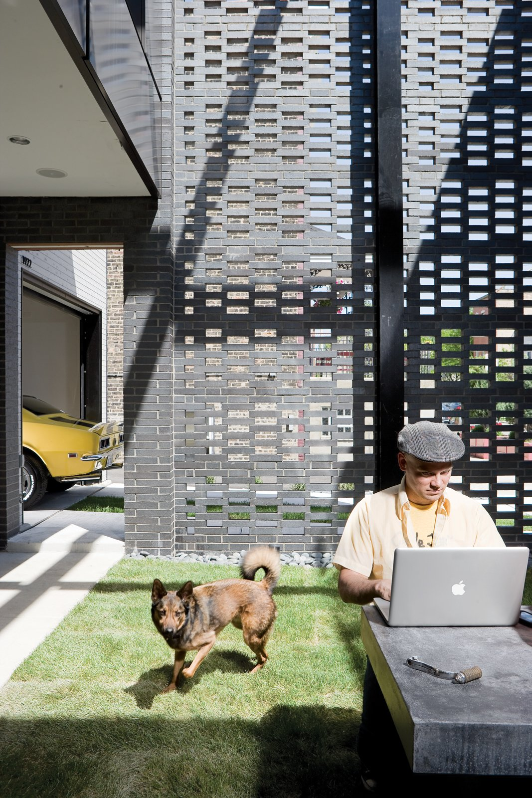 Outdoor and Grass David Hernandez and Jack enjoy the house's walled garden.  Photo 4 of 10 in The Brick Weave House in Chicago