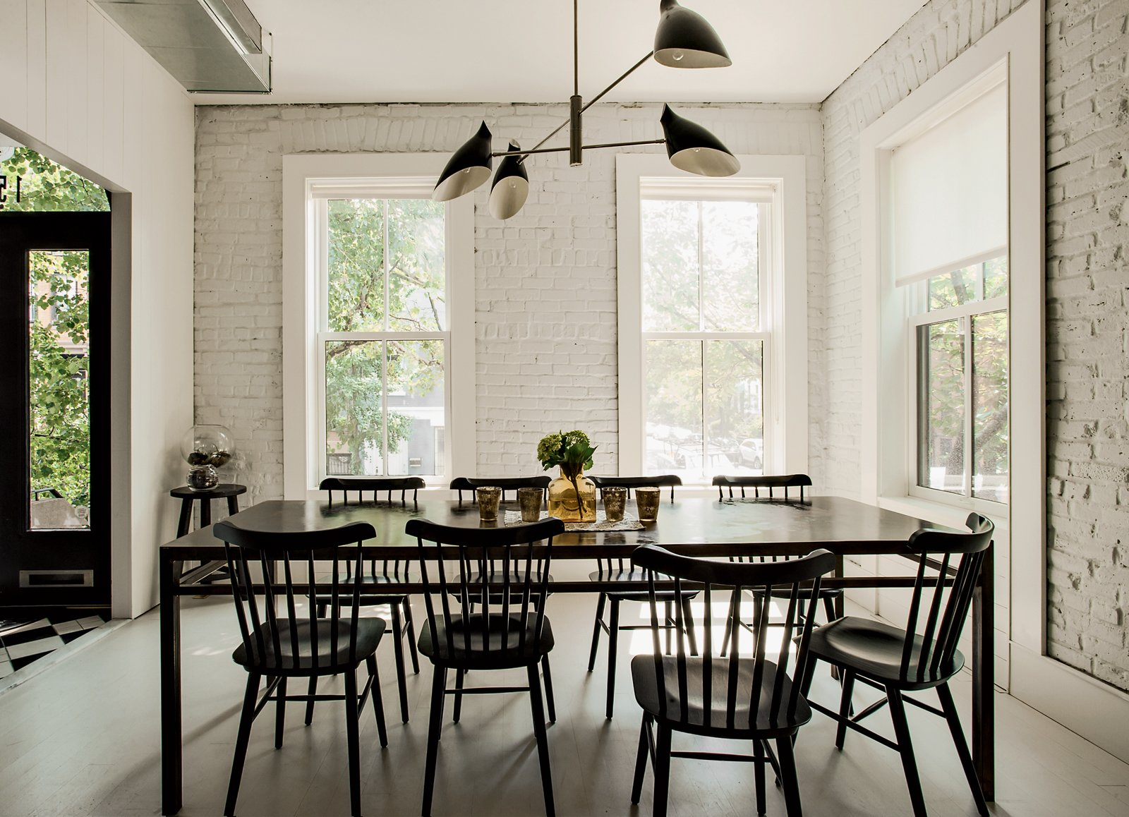 Dining Room, Pendant Lighting, Table, and Chair The Torroja pendant light by David Weeks hangs in the dining area, standing in sharp relief to the home's original brick, now painted white (in Benjamin Moore Paper White)along with the wooden floorboards (in Benjamin Moore Revere Pewter). Radiant heat underfoot means a toasty interior even without a surfeit of textiles. Photo by Matthew Williams.  Modern Brick Homes by Kelsey Keith