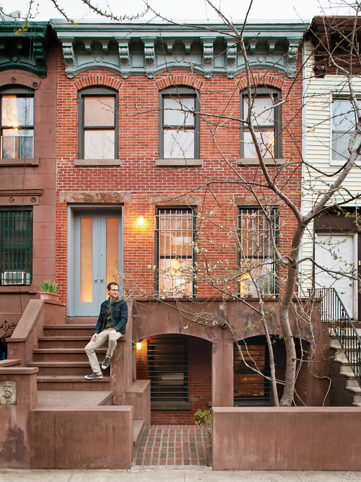 Sherman sits in front of his Prospect Heights home. The front door is made from etched Lexan bulletproof glass.  New York City Row House Renovations We Love by Zachary Edelson