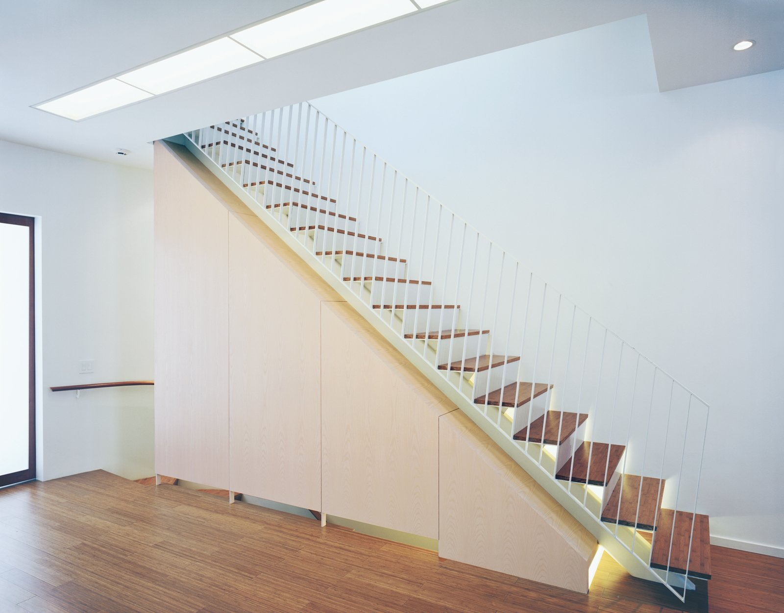 Staircase, Metal Railing, and Wood Tread Briggs and Knowles's elegant staircase draws upon the language of the oculus; the stairs are underlit with fluorescent lighting, which accents the line of the steps, giving them an ethereal, almost weightless quality.  190+ Best Modern Staircase Ideas from Modern Rowhouse Renovation in New York