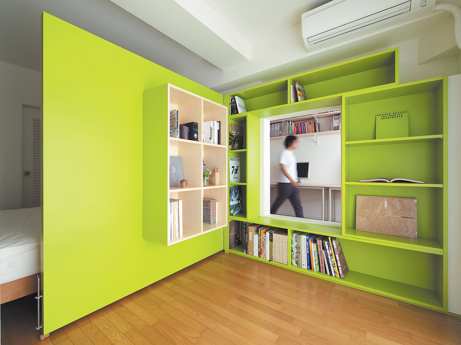 Shibata wanted more shelf space in her home office, so she added a plywood door with built-in bookshelves that opens into her bedroom to form a reading nook. Glimpsed from the adjacent room, the space looks larger than it actually is, thanks to the bright green walls.  Home Offices and Workspaces We Love from This Shape-Shifting Apartment Lets an Architect Work from Home