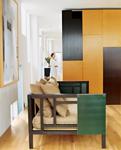 Operable panels of the built-in cabinetry, in chocolate and caramel colors, offer cues to the color palette of more mobile furnishings. Using the same panel material, the architect customized a West Elm couch for the living room.