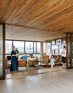 São Paulo architect Isay Weinfeld's Casa Deck offers cinematic vistas, a lush garden, and a retreat from Brazil's largest city. With São Paulo on one side and a terrace and garden on the other, the Strozenbergs' living room feels vast. The sofa is a Harry Large by Antonio Citterio for B&B Italia and the coffee table behind Ticiana Strozenberg (with baby) is a vintage design by Geraldo de Barros. The custom wood paneling throughout the house is by Fiamoncine, as are the window treatments. Photo by Matthew Williams.