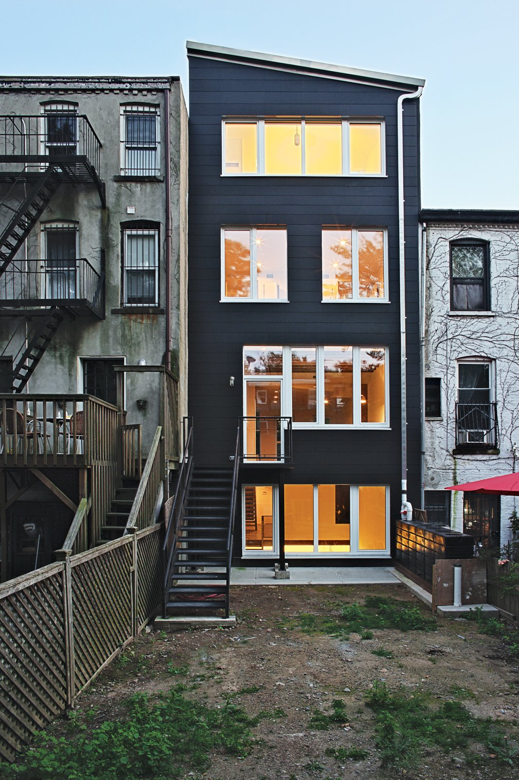 Exterior, Shed RoofLine, and House Building Type The rear facade, like the top-floor addition, is faced in rectangular panels of black rainscreen Richlite over exterior mineral wool insulation.  Super-Insulated Houses That Stand Up to Winter's Chill by Heather Corcoran from A Sustainable Brownstone Transformation in Brooklyn