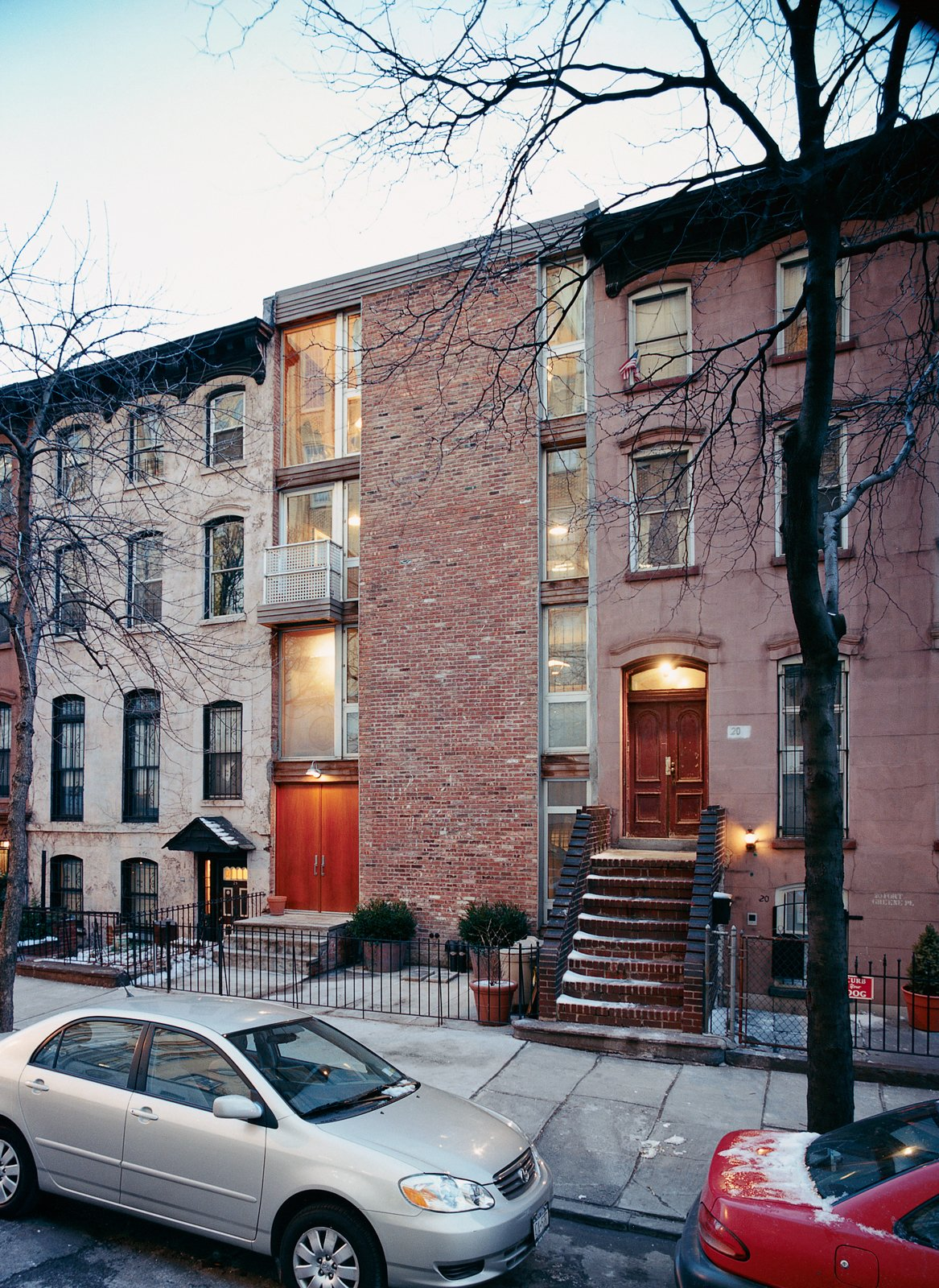 Though the couple's house is much younger than its immediate neighbors, it manages to fit right in—adding to, rather than detracting from, the neighborhood's historic character. Tagged: Exterior, Brick Siding Material, and Flat RoofLine.  Photo 3 of 5 in A House Grows in Brooklyn