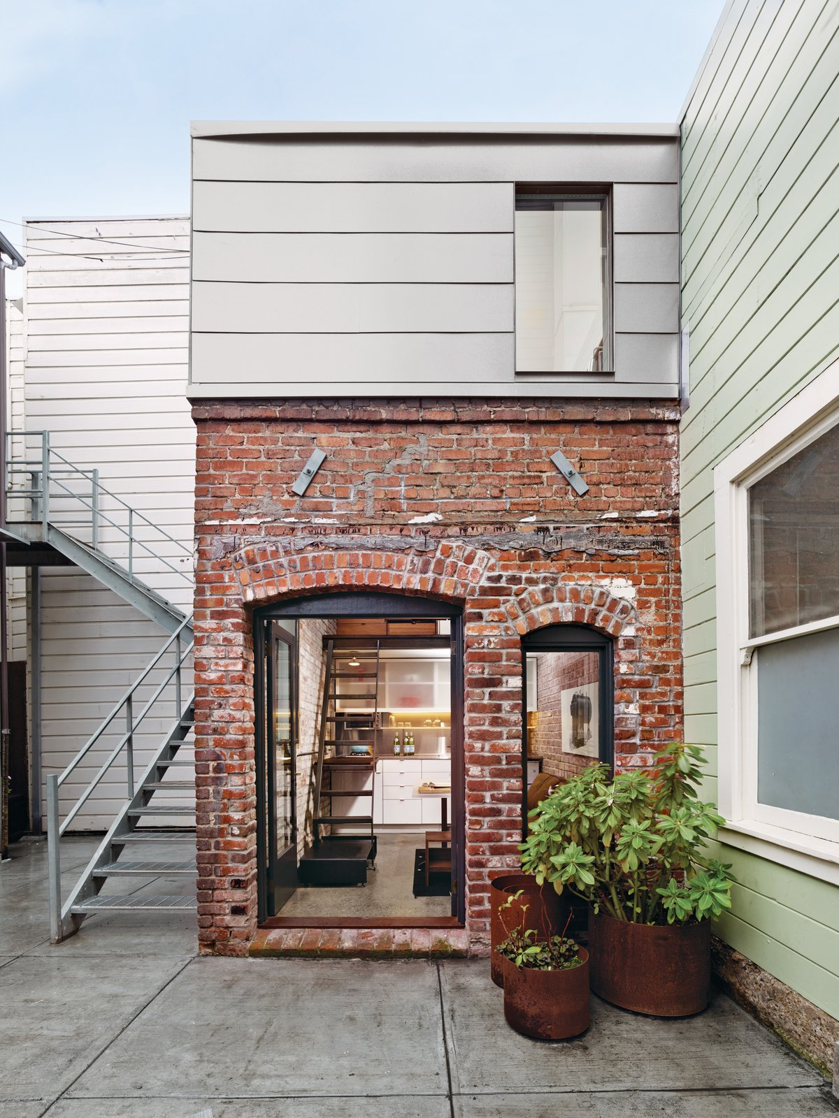 Concrete, Small, Back Yard, Exterior, House, and Brick A COMPACT THREE-STORY BRICK LOFT IN SAN FRANCISCO  Making the most of vertical space unleashes the potential of a petite San Francisco project.  Photo by Cesar Rubio.  Best Exterior Concrete Photos from A Compact Three-Story Brick Loft in San Francisco