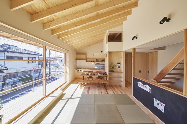 The 13-foot-wide sliding window provides abundant natural light year-round. The staircase was placed at the building's center to maximize openness and make space for the carport below. The blackboard is for the couple's young son, Takuma, to play with and practice writing.