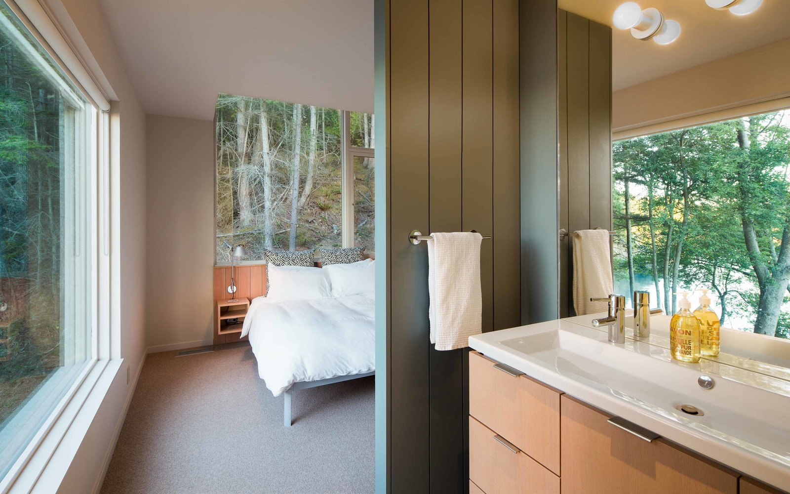Bath Room A Design Within Reach bed is steps away from a Second Floor sink by Duravit that's outfitted with an Essence Grohe faucet. Benjamin Moore's Templeton Gray is painted on the master bathroom's wood paneling.  San Juan Islands Residence by Kelly Dawson