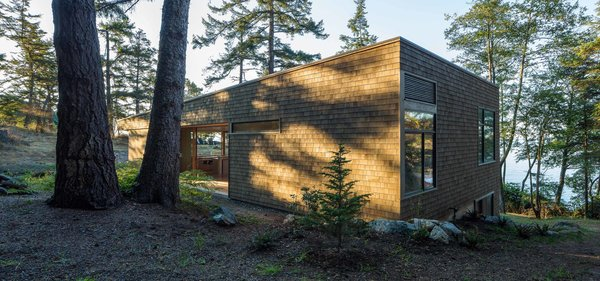 """""""The liberal use of wood roots the structure in the landscape and provides the owners with an experience strongly connected with location,"""" Herrin says. The exterior's Western red cedar shingle siding has a semi-transparent stain, half Fieldstone and half Burnt Hickory from Cabot."""