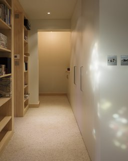 The flat is approximately 195-square-feet, forcing a level of economy in the design. This hallway leads to the entrance, as well as provides access to a storage room and bathroom.
