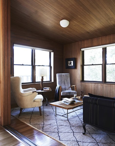 The cozy interior is wrapped in hemlock wood, which Esherick also used in the house he designed following this one in the Kent Woodlands area. A Thonet chair joins a Ben Soleimani rug for Restoration Hardware in the seating area.