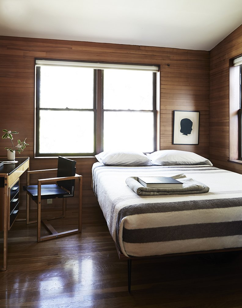 Bedroom, Bed, and Dark Hardwood Floor The rooms, featuring sloped ceilings, feel small and intimate. In the guest bedroom, there is a custom bed and a Swedish school desk found on eBay.  Bedrooms by Dwell from Looking Good for Over 70 Years: This Cozy Joseph Esherick Home is Amazingly Well-Preserved
