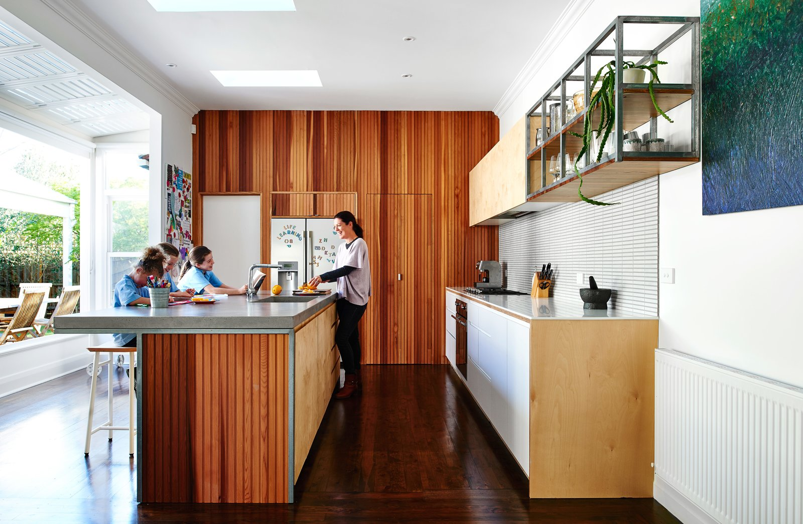 Kitchen, Refrigerator, Cooktops, Wood, Concrete, White, Dark Hardwood, Recessed, Wall Oven, Undermount, Ceramic Tile, and Range Hood Australian expats Carla and Paul Tucker tasked designer Dan Gayfer with expanding their Melbourne bungalow without adding any square footage. In the kitchen, a soft palette of wood, laminate, and tile created cohesion, impressive considering the clients didn't see a single finish, color, or material in person prior to their homecoming. The kitchen cabinets were clad in Russian birch plywood, and the countertops were concrete.  Kitchen Cooktops Undermount Wall Oven Dark Hardwood Photos from Skype Lets a Family Renovate Their Kitchen 3,700 Miles Away