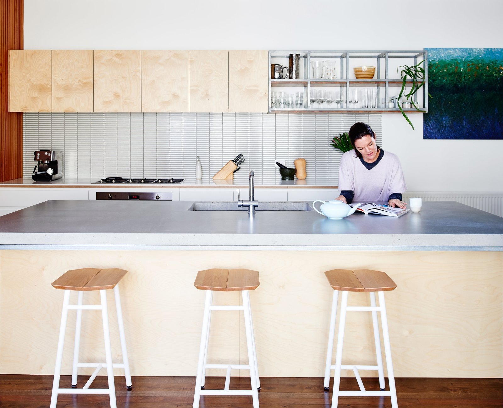 Kitchen, Range, Concrete, White, Wood, Open, and Dark Hardwood In the kitchen, Dedo stools by Simone Simonelli for Miniforms pull underneath a poured-in-place concrete countertop.  Best Kitchen Concrete White Photos from Skype Lets a Family Renovate Their Kitchen 3,700 Miles Away