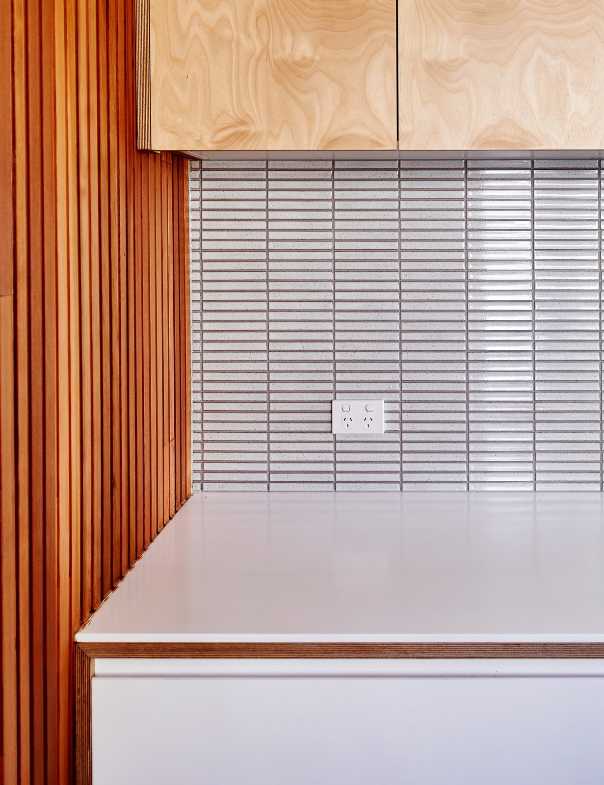 """Kitchen, White Cabinet, Wood Cabinet, and Ceramic Tile Backsplashe A wall of three-inch-wide cedar slats contrasts with the tile backsplash.  Search """"cedar"""" from Skype Lets a Family Renovate Their Kitchen 3,700 Miles Away"""