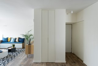 The clients were expecting their second child and it was important that there was as much space as storage. Studio Bazelet found a clever solution by building a slender closet behind the living room wall and custom furniture with storage.