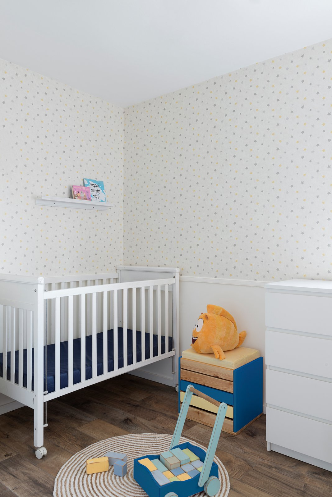 Although the color palette is minimal, the couple added bursts of blue and yellow throughout the home in the living room and even the new nursery.  Photo 2 of 20 in 20 Cool Cribs for the Modern Baby from Expecting Couples Will Understand, Storage Is Everything at This Apartment