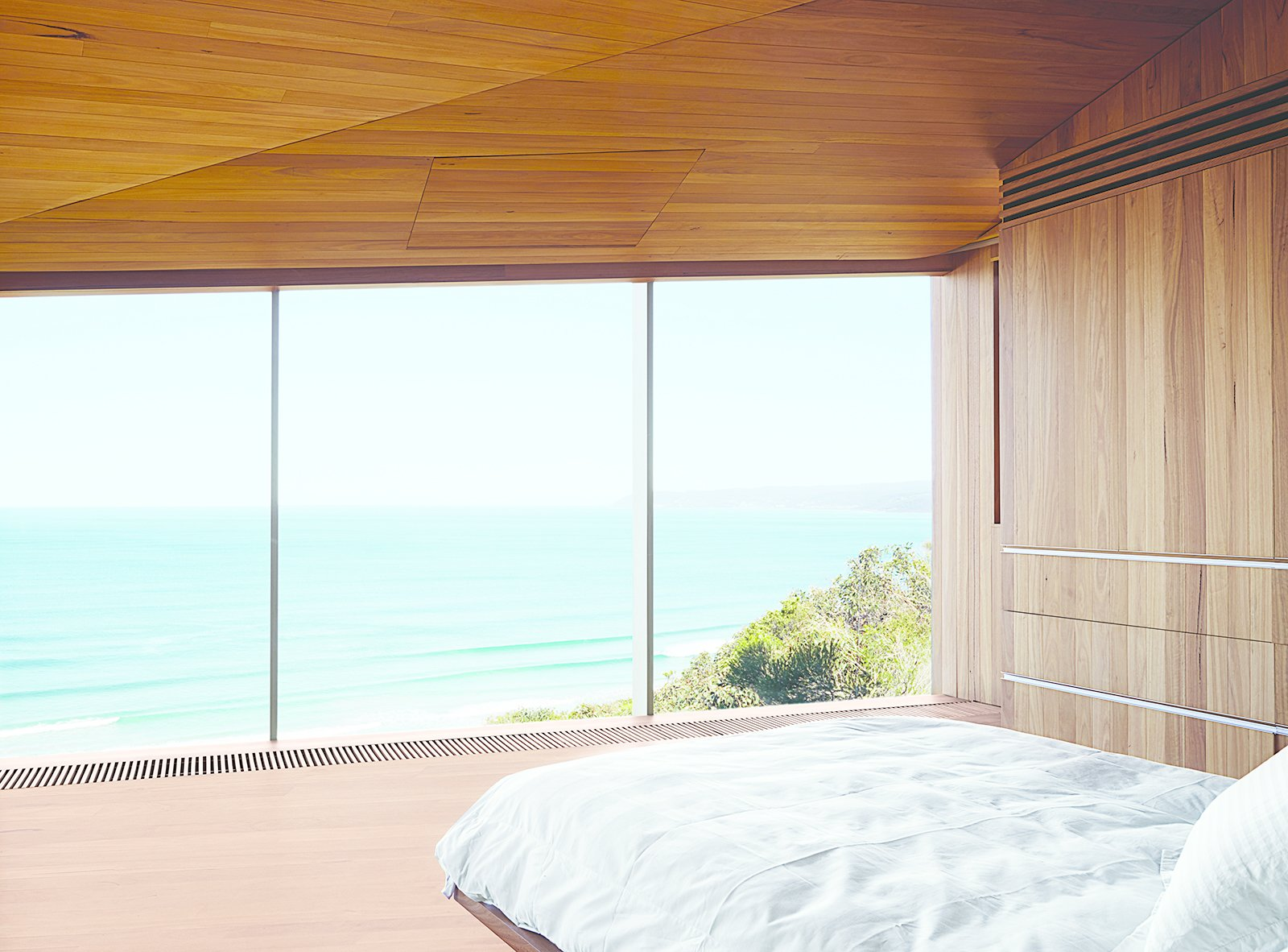 Bedroom, Bed, and Light Hardwood Floor The couple, both surfers and beach lovers, wake up to stunning views of the azure-blue Southern Ocean in their otherwise monochromatic eucalyptus master bedroom. Wardle's firm designed the bed base, and the panel in the ceiling hides a television.  Photo 7 of 9 in A Eucalyptus-Lined Oceanfront Home in Australia