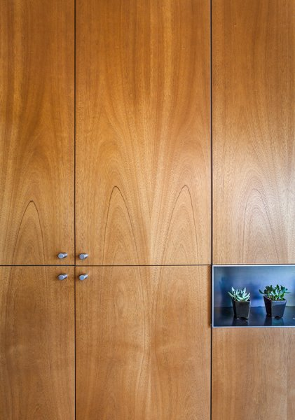 Cabinetmaker Ben Wilborn carefully matched the grain of the cabinets, which hold everything from dishes to a television, while a steel niche for the dining table leaf doubles as a display space.