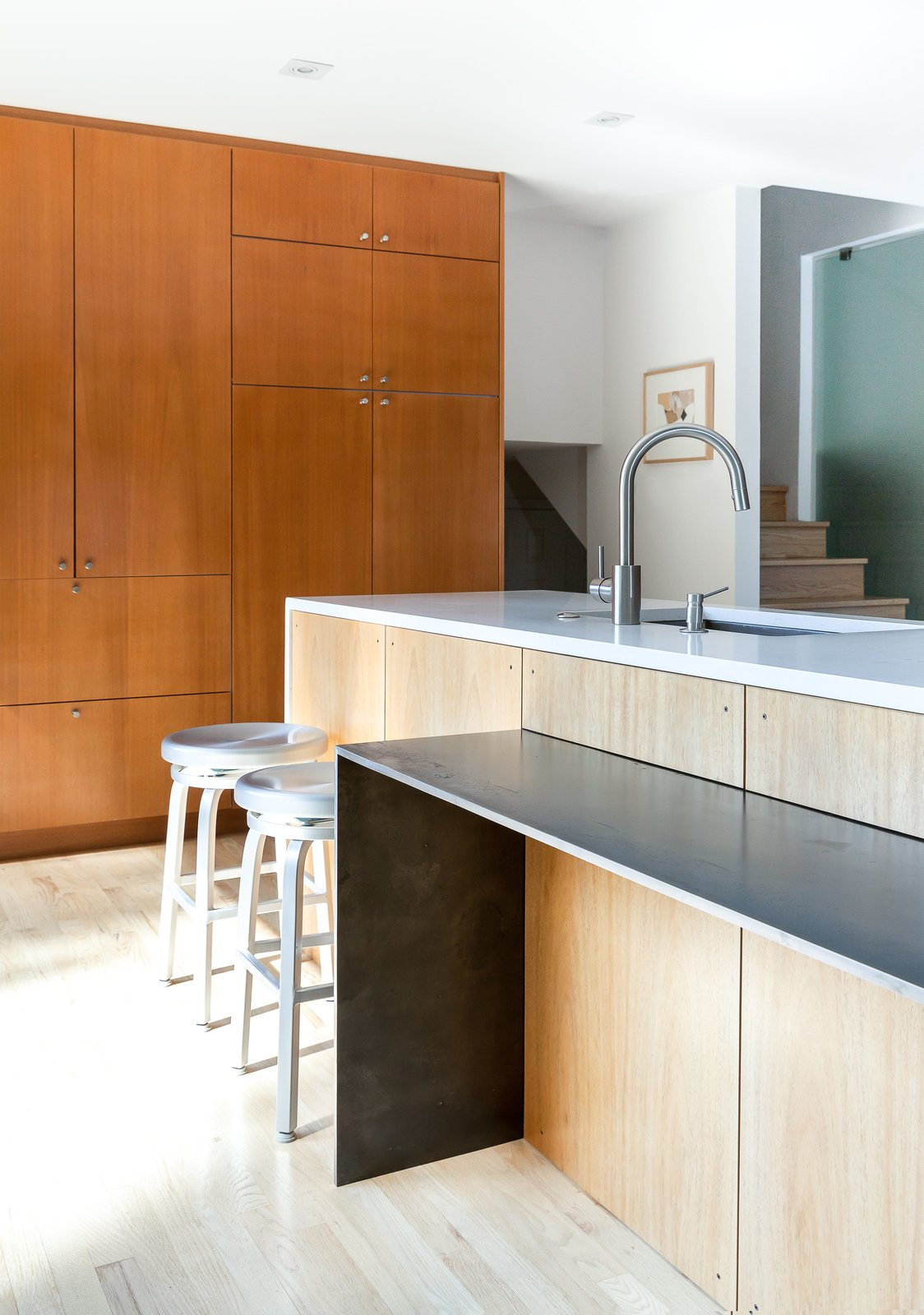 Kitchen, Wood Cabinet, Light Hardwood Floor, Recessed Lighting, and Undermount Sink The dining table narrows to a counter attached to the island.  Photo 7 of 11 in A Completely Dysfunctional Nevada Kitchen Becomes Everyone's Favorite Spot for Parties