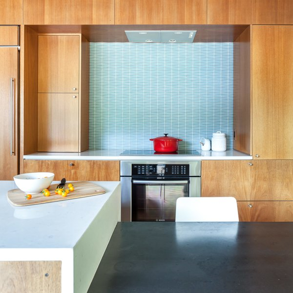 The stools are from Crate & Barrel. The Hobsons chose a geometric-patterned glass tile backsplash by Island Stone. Induction cooktop and oven are by Bosch.