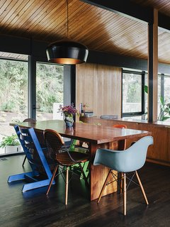 An assortment of dining chairs, including vintage iterations on the Eames shell chair by Charles and Ray Eames and Stokke's Tripp Trapp chair, are clustered around a table lit by a pendant lamp by Coco Flip Design Studio.