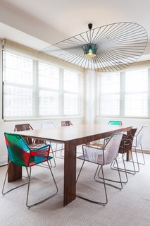 In the Tribeca penthouse of a young bachelor, Reddymade Design kept most of the space intact, focusing on adding bright and appealing furniture and materials. Tropicalia chairs from Moroso surround an El Dom table from Cassina. The pendant is from Petite Friture.