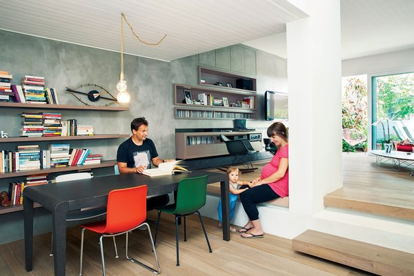 HAL Tube and Sledge chairs, by Jasper Morrison for Vitra, are arranged around an Extesso dining table by Neo Katoikein. A George Nelson Eye Clock sits on the cantilevered shelving by Pafos, a furniture company based in Oinofyta, Greece, which also constructed the built-in cabinets in the living room. The pendant lamp includes fixtures designed by Lee Broom for Oikos.