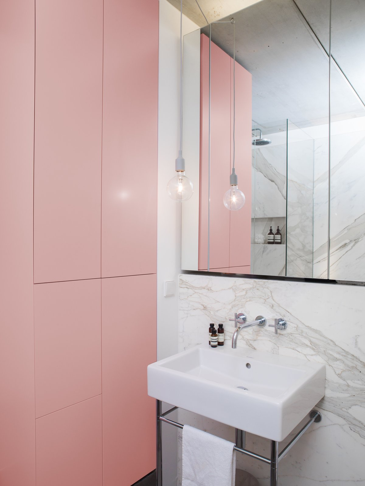 Bath Room, Pendant Lighting, Marble Wall, Wall Mount Sink, Corner Shower, and Pedestal Sink Statuario marble appears again in the bathroom, where it contrasts pink cabinets that create ample room for storage.  This Berlin Apartment Manages to Be Totally Adorable in Only 900 Square Feet by Allie Weiss