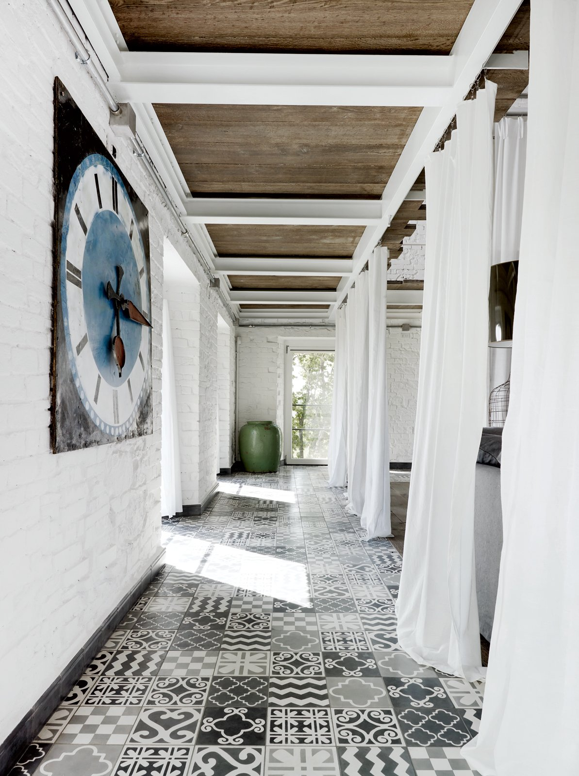 Hallway and Ceramic Tile Floor A carpet of custom tile created by Navone punctuates a corridor on the first floor.  Photo 4 of 11 in Paola Navone's Industrial Style Renovation in Italy